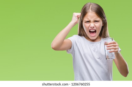 Young beautiful girl drinking glass of water over isolated background annoyed and frustrated shouting with anger, crazy and yelling with raised hand, anger concept