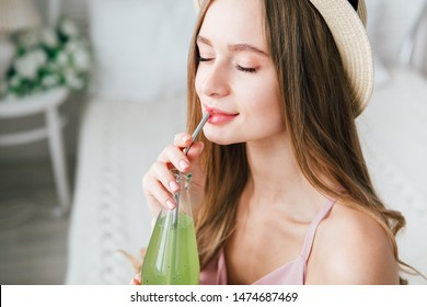 Young beautiful girl drinks a healthy green drink with Basil seeds through a reusable metal tube. The concept of healthy nutrition, environmental friendliness and zero waste. Toning.