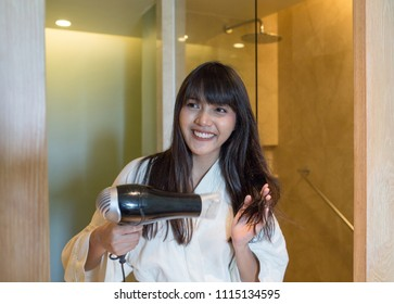 Young beautiful girl drying her hair after bathing in the bathroom