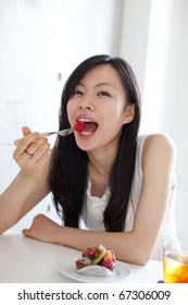 Young beautiful girl eating dessert