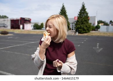 Young beautiful girl eating hot dog in the parking lot.