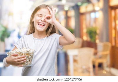 Young beautiful girl eating popcorn snack isolated background with happy face smiling doing ok sign with hand on eye looking through fingers