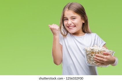 Young beautiful girl eating popcorn snack isolated background screaming proud and celebrating victory and success very excited, cheering emotion