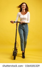Young beautiful girl with electric scooter. Isolated on yellow background. Technology and freedom of movement.