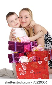 young beautiful girl embracing her little brother near the gifts