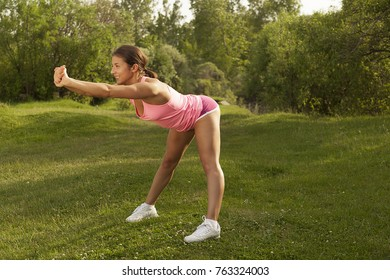 young beautiful girl is engaged in morning gymnastics, sports exercises and fitness in the park, training