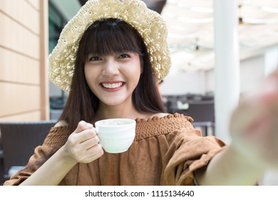 Young beautiful girl enjoy and relaxing  her breakfast in the outdoor atmosphere restaurant, Thailand