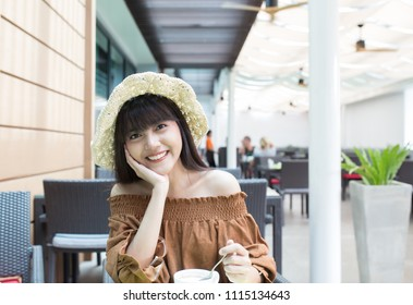 Young beautiful girl enjoy and relaxing with her breakfast in the outdoor atmosphere restaurant