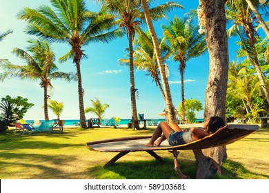 Young beautiful girl enjoy vacation on tropical paradise beach on background green palm tree and blue summer sky