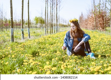 young beautiful girl enjoying nature in a field of beautiful yellow dandelions