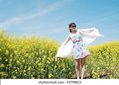 A young beautiful girl enjoying a sunny day in a field of canola flowers.