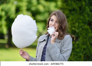 Young beautiful girl enjoying sweet cotton candy in spring green park