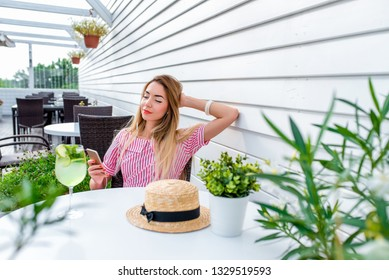Young and beautiful girl enjoys music in headphones in summer in cafe table. Happy phone hand, emotional pleasure. Online application in Internet playlist. Lunch and dinner in the restaurant.