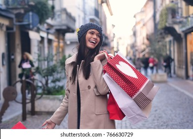 A young and beautiful girl enjoys shopping while shopping for the city's shops. The girl holds many handbags all colored. Concept of: shopping, fun, leisure, discounts and balances.