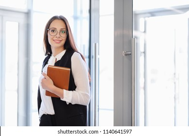 A young beautiful girl in eyeglasses enters glass office door.