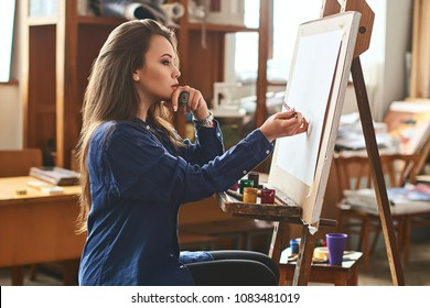 Young beautiful girl, female artist painter thinking of a new artwork idea and ready to make the first brushstroke on a wooden easel with a brush in studion interior