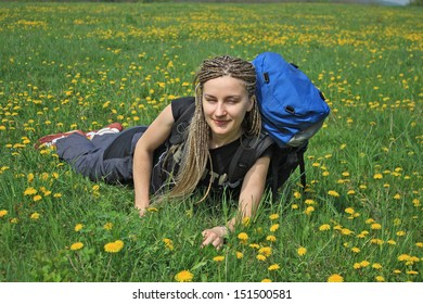 Young Beautiful Girl in Field of dandelions with African Braids and Backpack