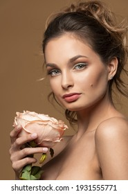 Young beautiful girl with flawless skin is holding pink rose flower on her hands. Skin care, beauty and cosmetics concept.