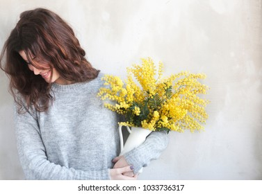 Young beautiful girl with flowers in hands, posing against concrete wall, minimalist style, mimosa in a flower pot