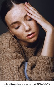 Young beautiful girl with freckles face in cozy knitted autumn sweater touching her face