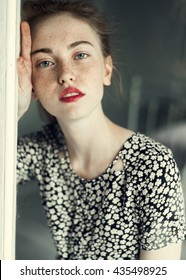 young beautiful girl with freckles at home near a window