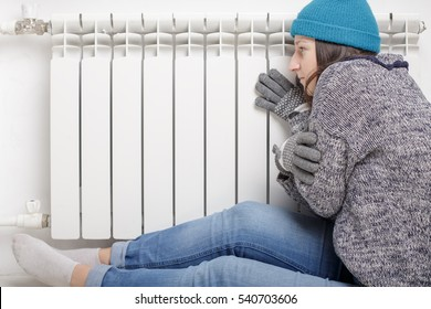 Young beautiful girl froze and warms hands near a radiator, dressed in gloves, a sweater and a hat