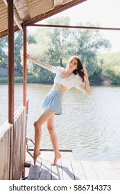 Young beautiful girl in the gazebo on the lake on a hot summer Sunny day. The concept of nature and relaxation. Toning.