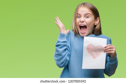Young beautiful girl giving mother father day card with red heart over isolated background very happy and excited, winner expression celebrating victory screaming with big smile and raised hands
