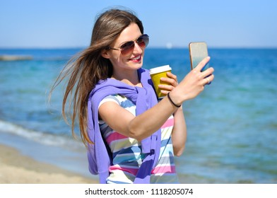 Young beautiful girl in glasses and with a cup of coffee makes selfie on the seashore