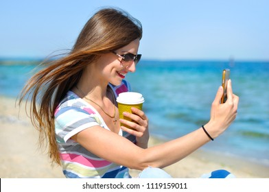 Young beautiful girl with glasses and a cup of coffee makes selfie on the seashore