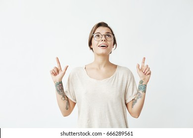 Young beautiful girl in glasses smiling pointing fingers up over white background.