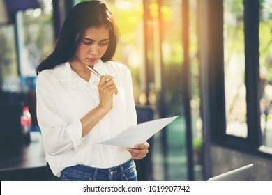 young beautiful girl in glasses thinks about something, holds a paper and a pen in her hands