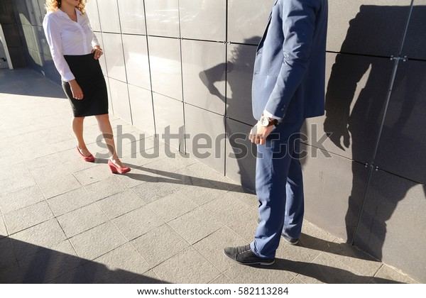 Young beautiful girl goes to meet, suited to young man, businessman, and they communicate, share ideas, smile, laugh, talk, solve problems on background of business center on open air. Guy dressed in