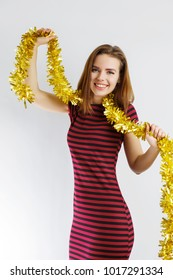 a young beautiful girl with a gold tinsel around her neck celebrating a holiday