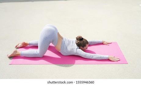 Young beautiful girl in gray clothes is practicing yoga on a pink brown background. Assana sports girl smiles. yoga for health pacification