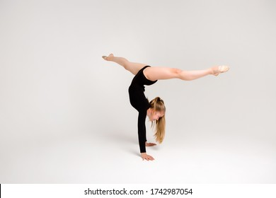 young beautiful girl gymnast on a white background. a young girl is engaged in gymnastics on a white background.