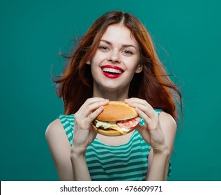 Young beautiful girl with a hamburger smiles and looks into the camera . Red lips