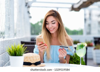 Young and beautiful girl happy smiling in summer cafe restaurant. In hand telephone and plastic credit card. Online application online banking, transfers money for lunch, happy shopping in store.