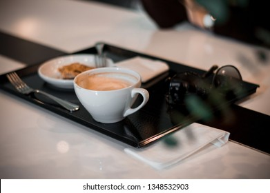 Young beautiful girl having coffee at the bar, cappuccino drink and cake on tray. Instagram friendly cafe place, black and white atmosphere with green flowers. Business style breakfast time.