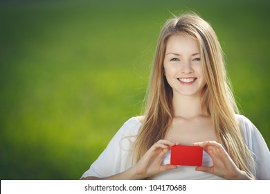 Young beautiful girl holding a blank credit card outdoor over green grass background