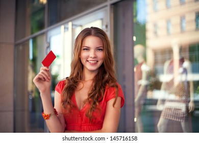 Young beautiful girl holding a blank credit card outdoor against store background