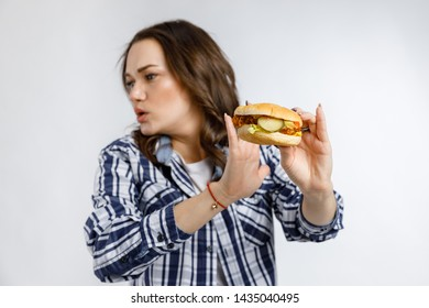 Young beautiful girl holding a Burger on a white background. Fast food, junk food, snack on the go.