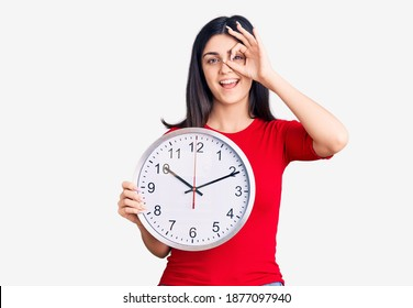 Young beautiful girl holding clock smiling happy doing ok sign with hand on eye looking through fingers