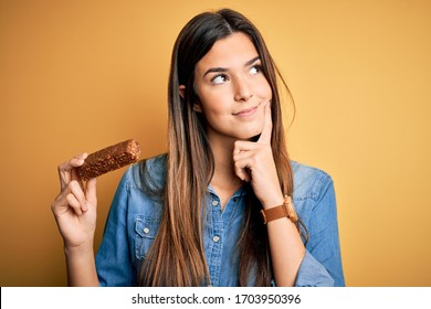 Young beautiful girl holding healthy protein bar standing over isolated yellow background serious face thinking about question, very confused idea
