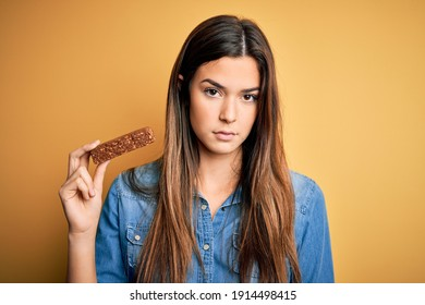 Young beautiful girl holding healthy protein bar standing over isolated yellow background with a confident expression on smart face thinking serious