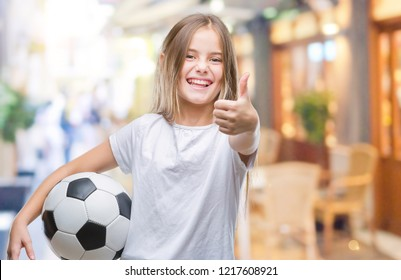 Young beautiful girl holding soccer football ball over isolated background happy with big smile doing ok sign, thumb up with fingers, excellent sign