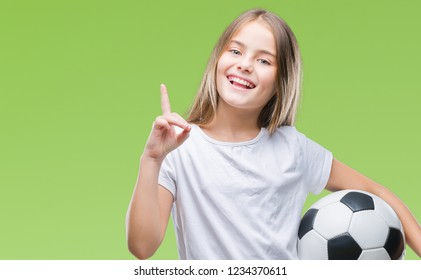 Young beautiful girl holding soccer football ball over isolated background surprised with an idea or question pointing finger with happy face, number one