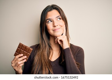 Young beautiful girl holding sweet bar of chocolate over isolated white background serious face thinking about question, very confused idea