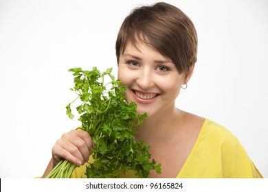 Young beautiful girl holding two bunches of parsley near the face