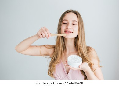 Young beautiful girl holding a useful bamboo toothbrush and a jar of tooth powder. The concept of a healthy lifestyle, environmental friendliness and zero waste. Toning.